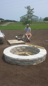 David takes a quick break after finishing the firepit installation.  This is locally quarried limestone that is cut to fit into a simple, but elegant firepit.  This is a 6' diameter pit, two course tall, with one cap stone course.  Beautiful huh?