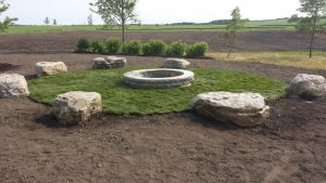 Close-up of the finished product – Natural seating stones, firepit, trees & shrubs & turf sod. What a combination :)?